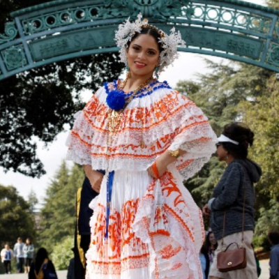 A young woman in traditional Latina dress stands under an arch