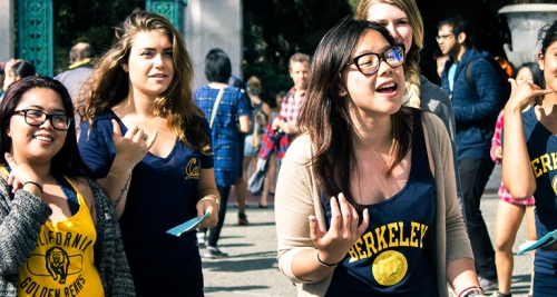 Group of 5 females students wearing UC Berkeley apparel are standing by Sather Gate in Sproul Plaza. 2 students wear glasses. The student to the far right is partly cut off from the image. The student in the front appears to be singing or talking. All the students are smiling.