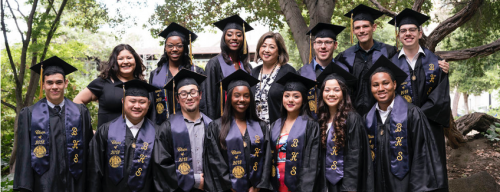 A group of twelve Hope Scholars in their caps and gowns smiling and posing for a photo with two faculty members