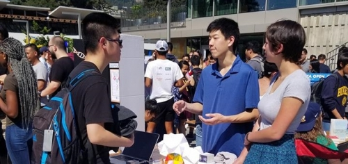 A student member of the organization is explaining his organization to a curious student who approached the organization's table, as another member of the organization looks on.