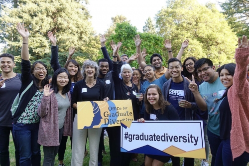 Members of the Office for Graduate Diversity smile and wave as they hold signs with the logo and hashtag of their organization emblazoned on the front.