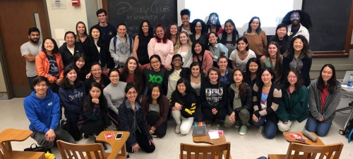 A very large group of smiling club members sitting and standing together, pose for a photo in front of a classroom chalkboard.