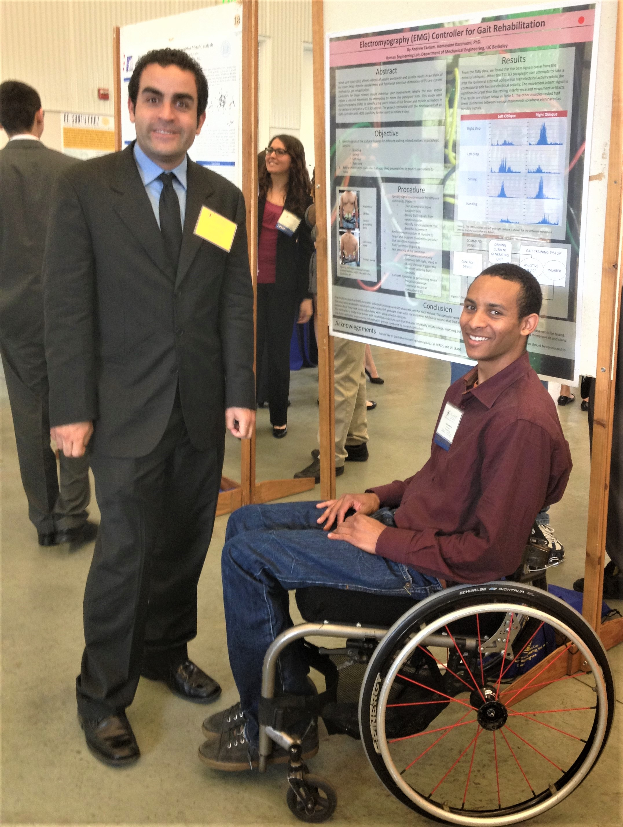 A man standing next to a male student research presenter, who is in a wheelchair, next to his research poster.