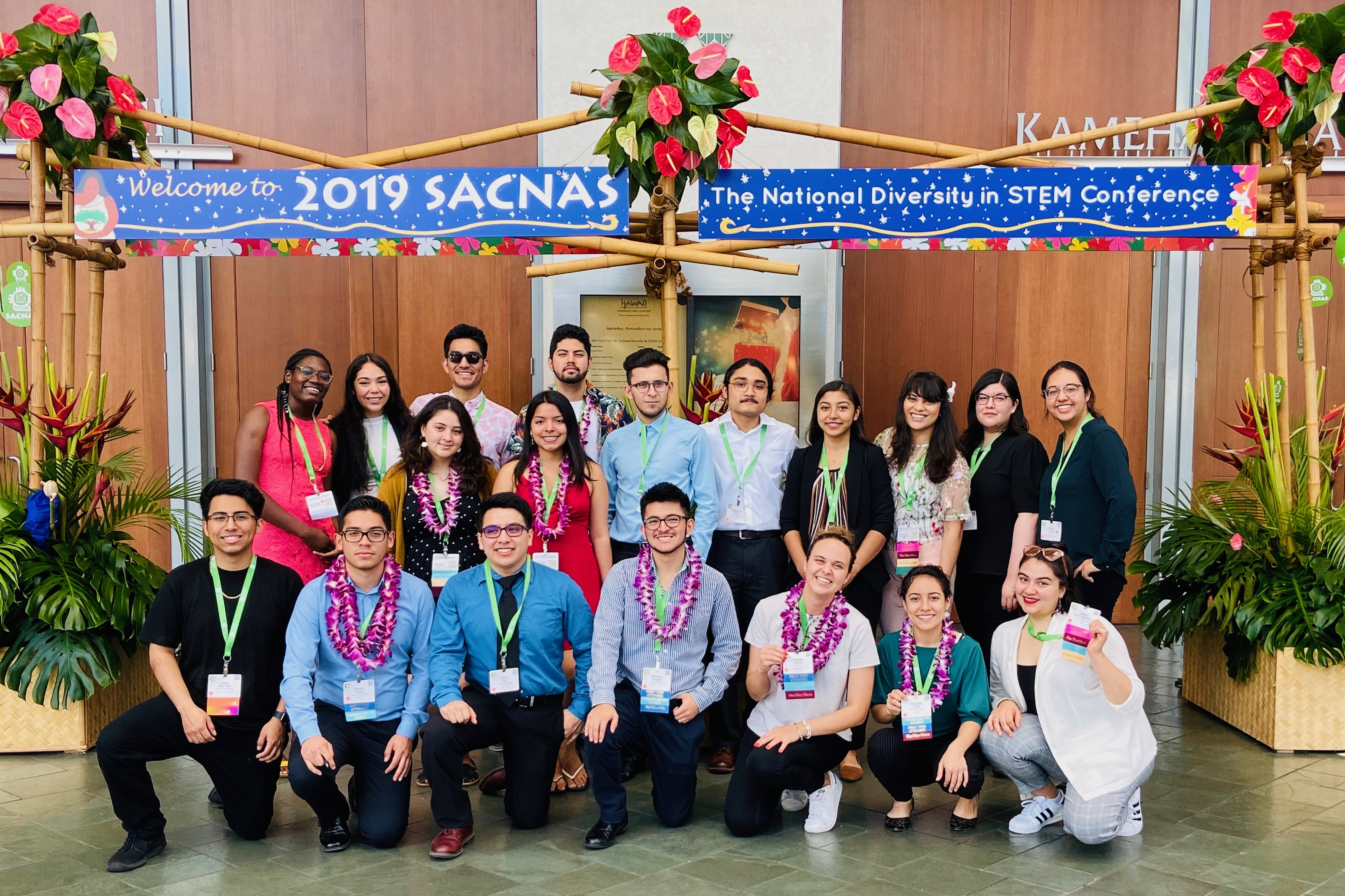 Nineteen people stand beneath a 2019 SACNAS banner wearing leis