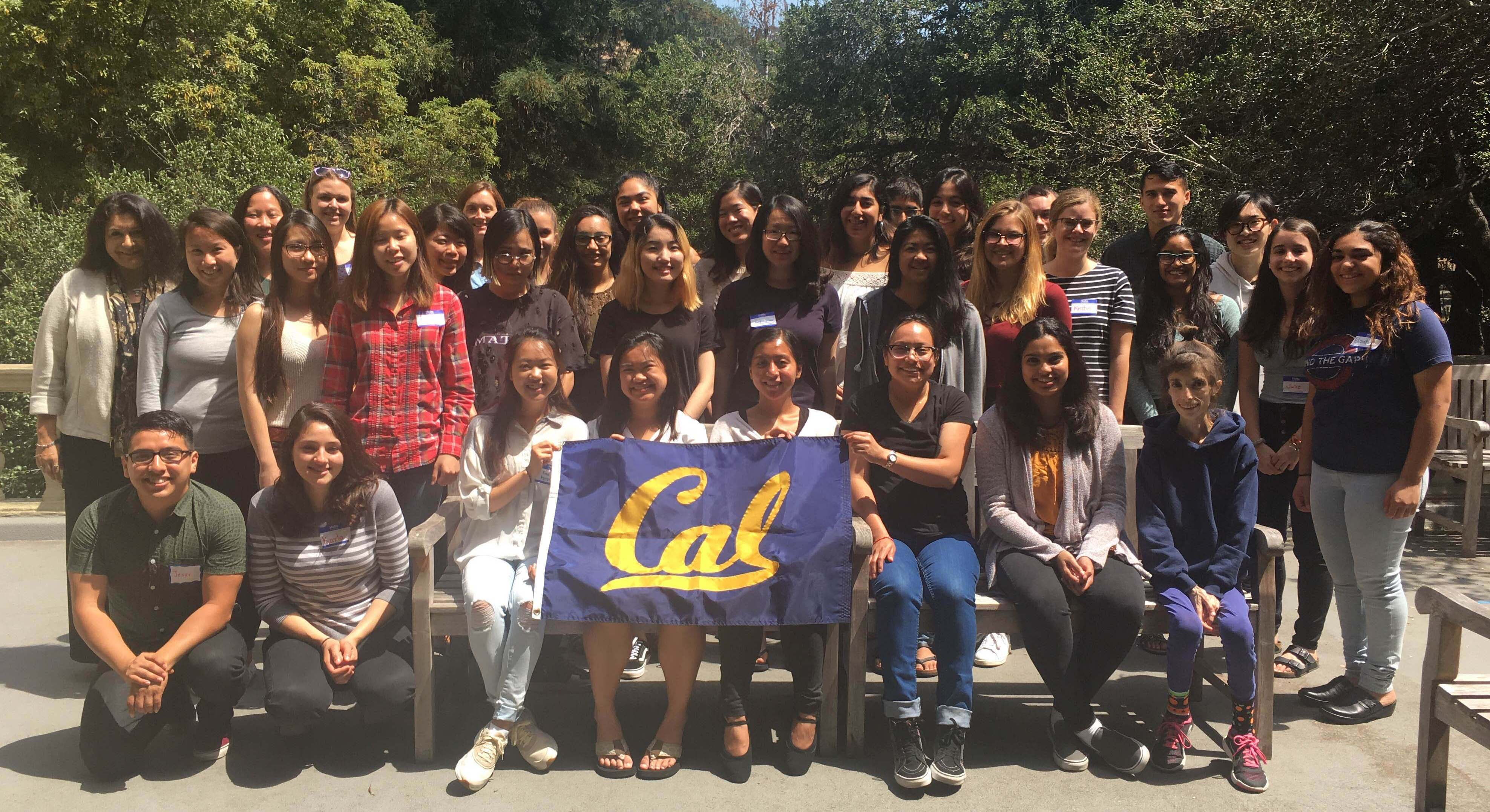 Large group of mostly female students posing for a photo holding a Cal banner on an outdoor patio with tall trees in the background at UC Berkeley.