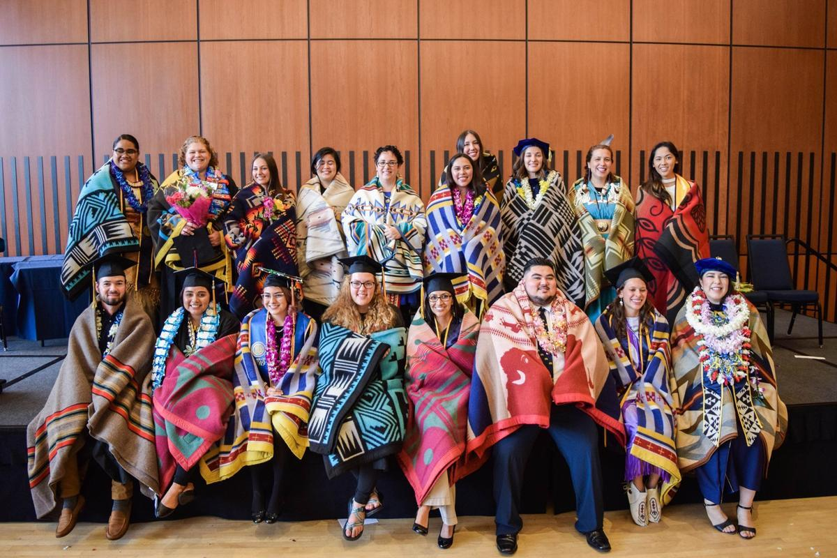 18 people wearing different colorful Native American blankets are smiling at the camera. Some students are wearing lei and graduation caps.