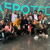 16 people are smiling and posing in front of what seems to be an AfroTech Conference Poster.